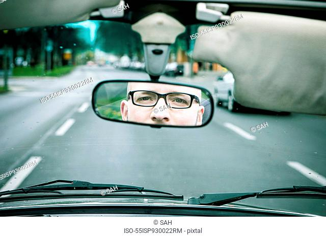 Reflection of young man wearing glasses driving car in rearview mirror