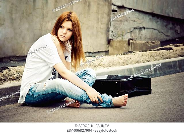 Beautiful young girl sitting on asphalt
