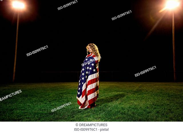 Girl wrapped in american flag at night