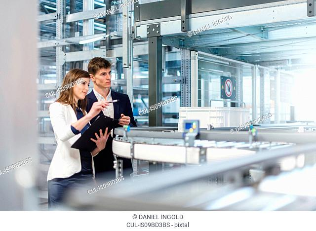 Two colleagues in industrial building, having discussion beside conveyor belt