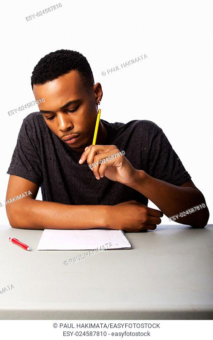 Handsome student thinking concentrating focussing for test examination sitting at desk, on white