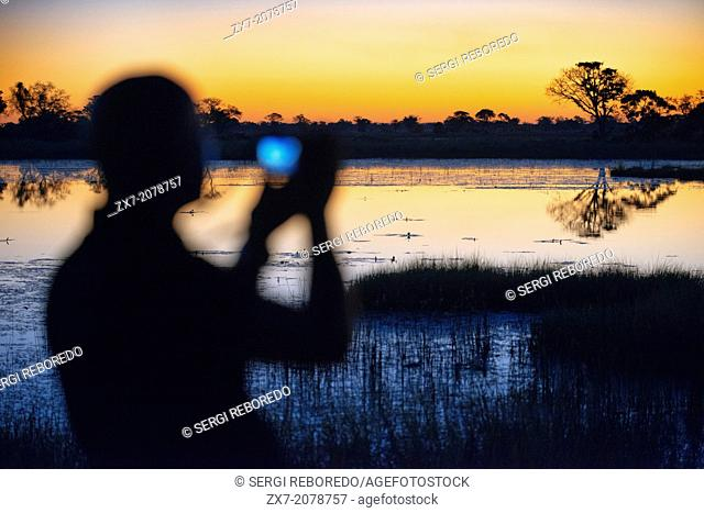 A man with binoculars enjoy the best sunsets in the Okavango Delta Eagle Fish Eagle Island Camp Bar Camp Orient Express