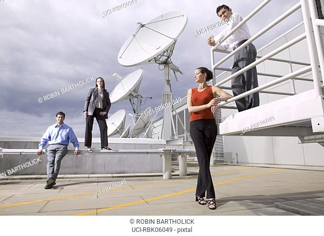Four people on roof near satellite dishes