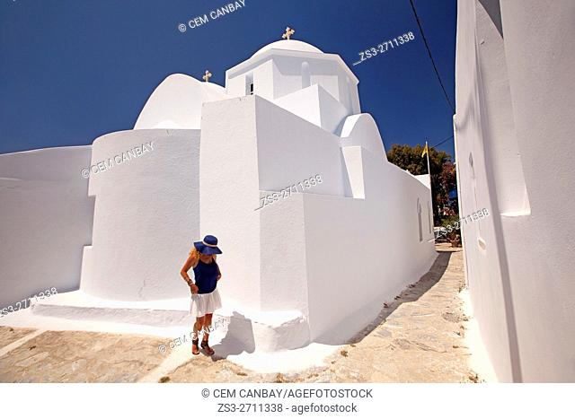 Tourist woman in front of a whitewashed church in the old town Chora, Amorgos, Cyclades Islands, Greek Islands, Greece, Europe