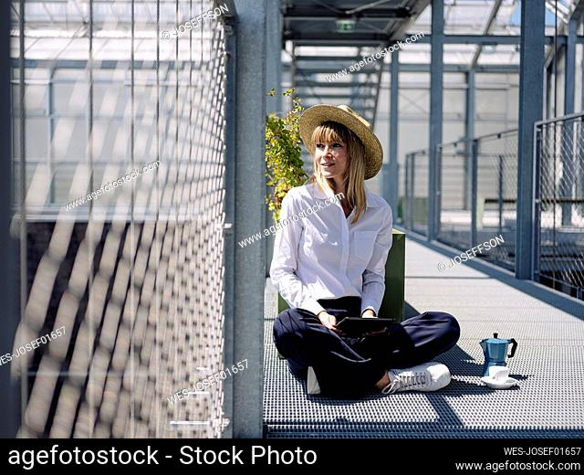 Businesswoman wearing hat using digital tablet while sitting by fence in greenhouse