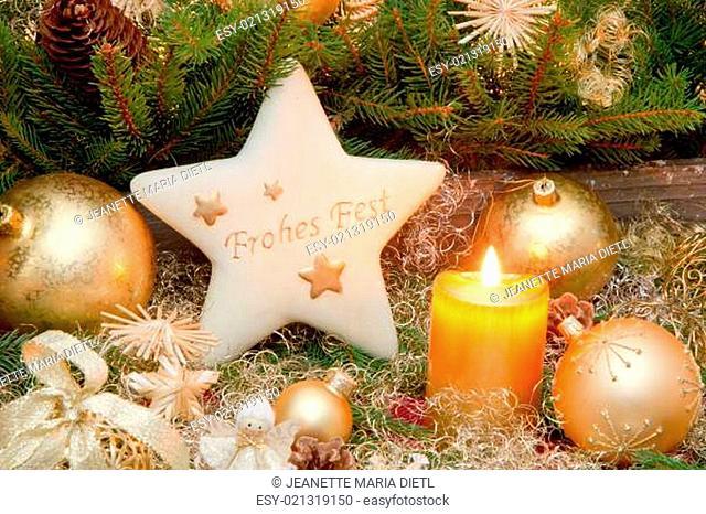 Golden christmas decoration with burning candle and german text Frohes Fest