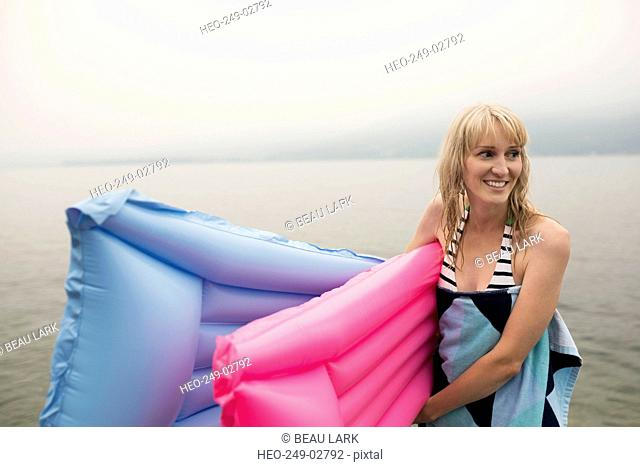 Smiling woman carrying pool rafts in lake