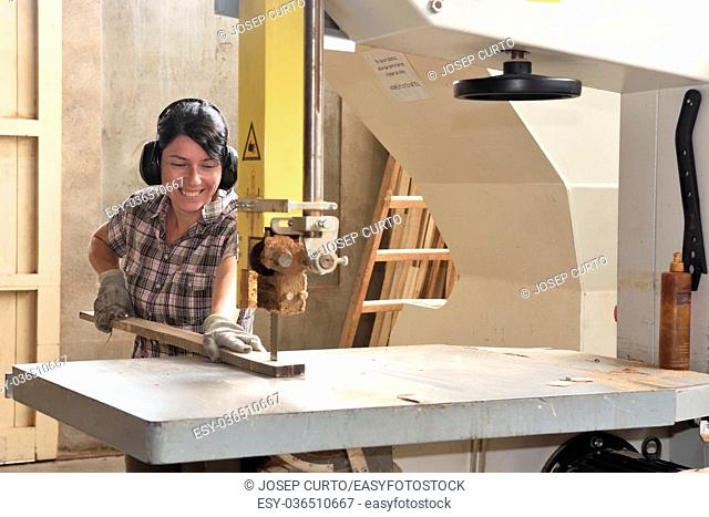a woman working in a carpentry workshop, sawing band