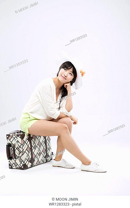 a woman sitting on a suitcase posing