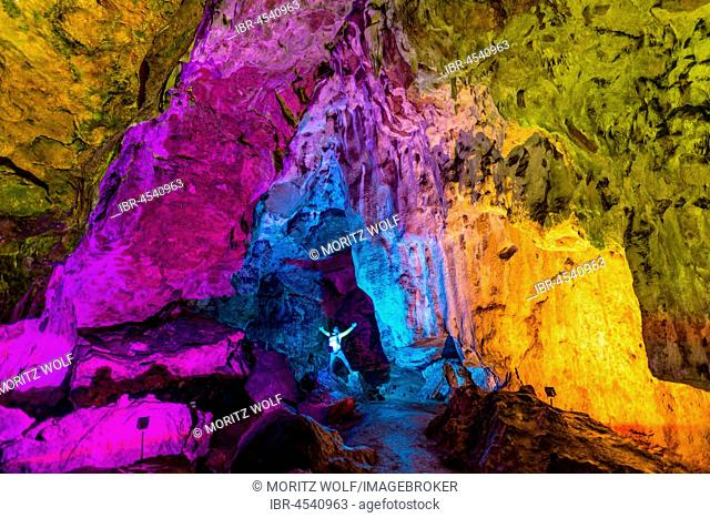 Man in a colourfully illuminated stalactite cave with stalagmites and stalactites, Nebelhöhle, Sonnenbühl, Baden-Württemberg, Germany