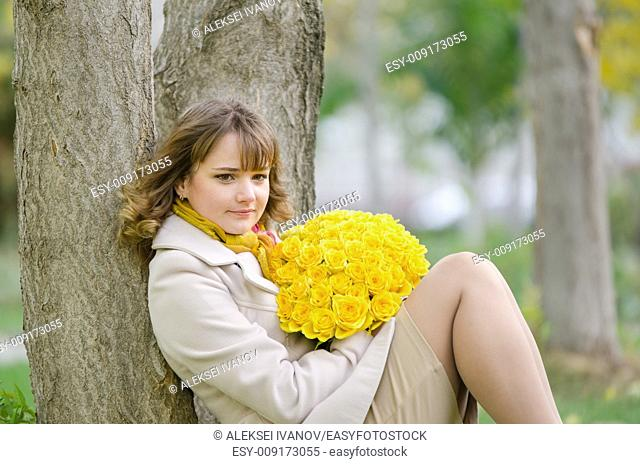 Young cute girl with a bouquet of yellow roses in autumn cool weather
