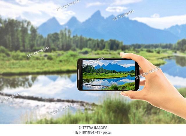 Hand photographing lake