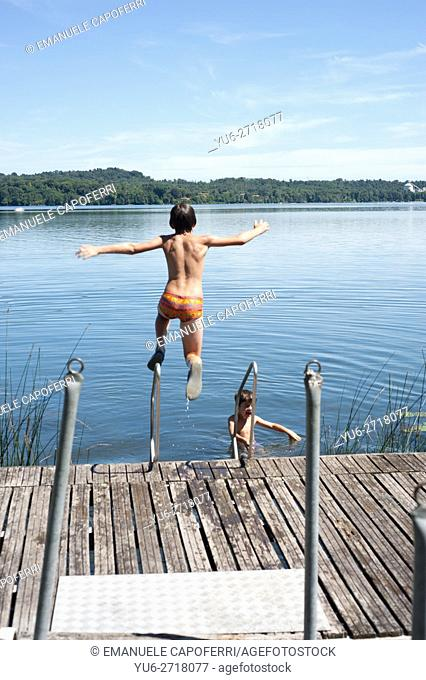 11 year old boy dives into the water of Lake Monate, Italy
