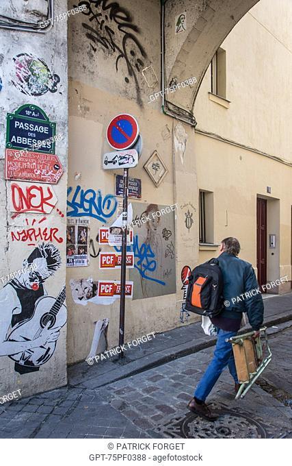 MAN WALKING ALONG PASSAGE DES ABBESSES, 18TH ARRONDISSEMENT, PARIS, FRANCE