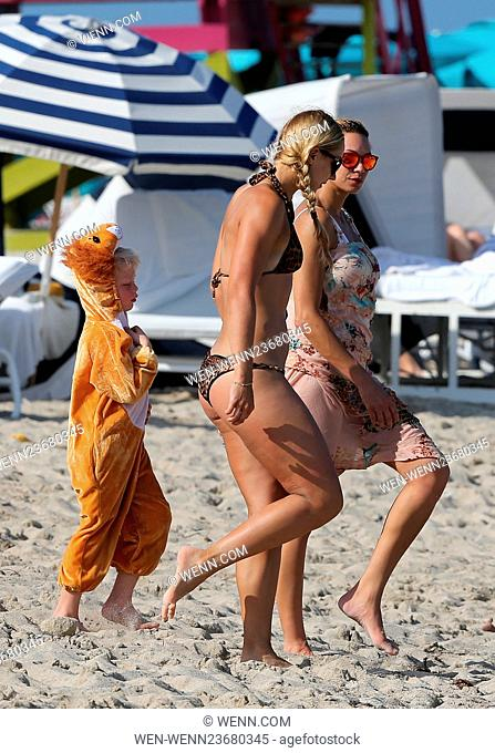 Lilly Becker shows off her beach body in a white one piece swimsuit as she takes her son Amadeus, who was dressed in a lion costume