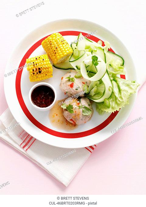 Plate of corn with cucumber salad