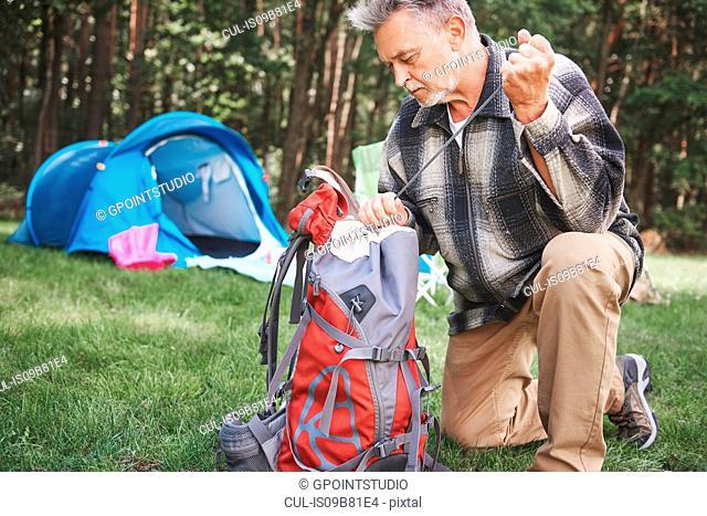 Senior man beside tent, packing rucksack