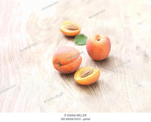 Peaches whole and half on wooden table
