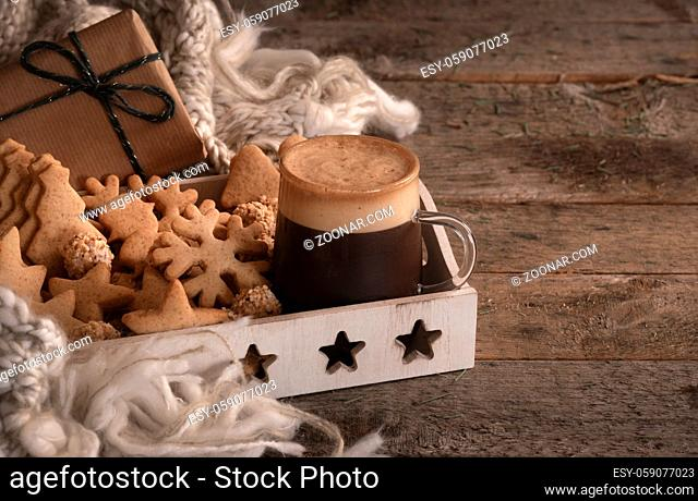 Christmas breakfast table with a tray full of gingerbread cookies, a cup of coffee, a wool scarf, and a gift, on a vintage wooden table