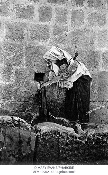 A woman washing clothes at the Well of Philippus, Holy Land