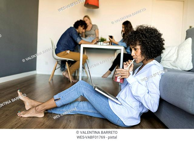 Woman with soft drink sitting on floor using laptop with friends in background