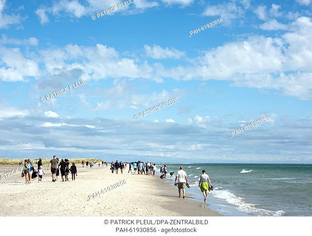 Tourists on the beach of Denmark's northernmost tip where the North Sea (from the left) and the Baltic Sea (from the right) encounter in Grenen, Germany