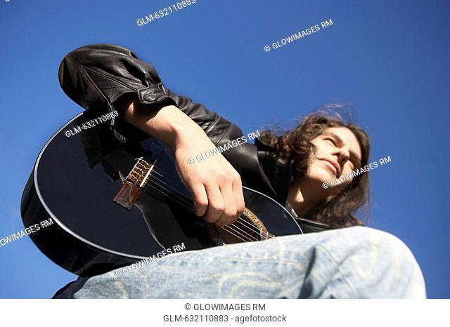 Low angle view of a young man playing the guitar