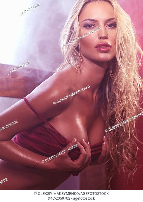 Sensual portrait of a glamorous sexy young woman with long blond hair taking her shirt off