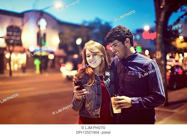 A young couple walking down a sidewalk in a popular area at dusk while looking at a smart phone; Edmonton, Alberta, Canada