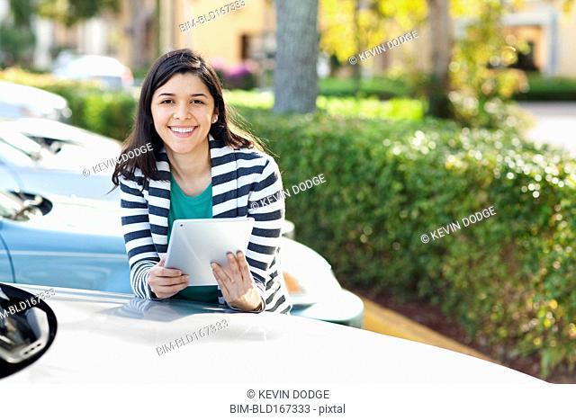 Hispanic woman using digital tablet in parking lot