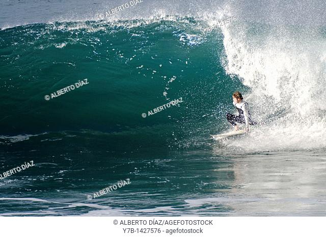 Surfer riding the waves of Paul do Mar on the island of Madeira, Portugal