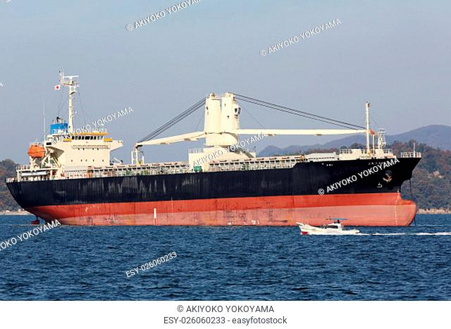 large cargo ship and fishing boat against blue sky