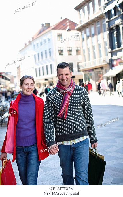 Mid adult couple walking at street with shopping bags