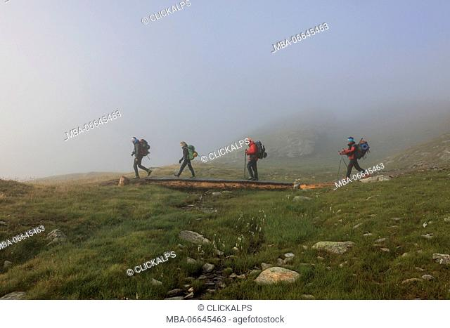 Hikers in the misty landscape at dawn Minor Valley High Valtellina Livigno Lombardy Italy Europe