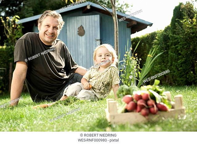 Germany, Bavaria, Father and son sitting in garden, smiling, portrait
