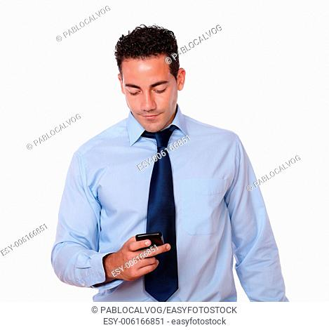 Portrait of a handsome young man on blue shirt and tie sending a message by cellphone on isolated background