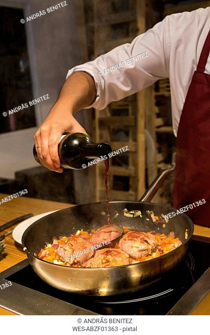 Man pouring wine on beef cheeks in a pan with sauteed vegetables
