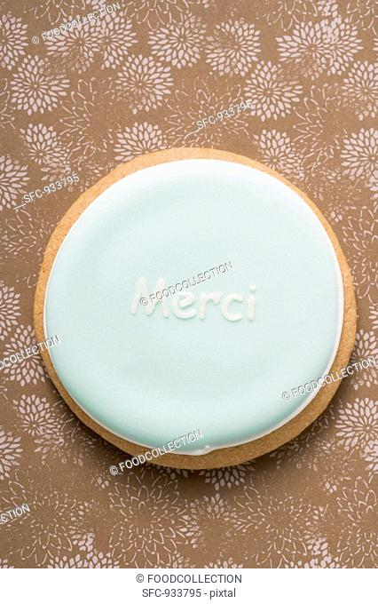 A pastel-coloured biscuit with the word 'Merci'