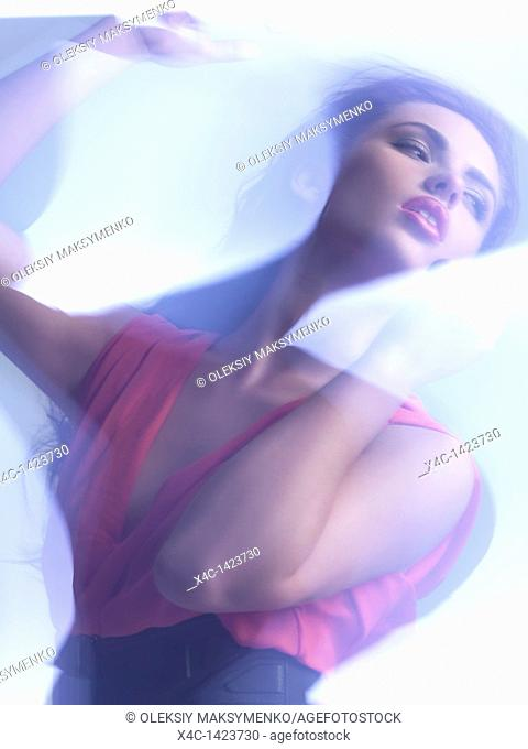 Futuristic dynamic beauty photo of a young woman wearing a red dress in shiny neon light settings  The photo has a slight motion blur due to its nature  The...