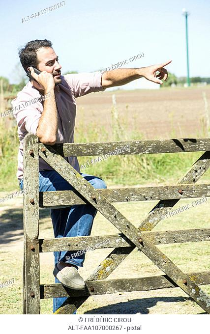 Farmer making phone call to report problem on farm