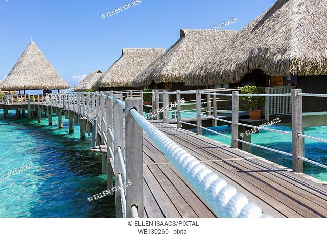 Walkway leading to luxurious overwater bungalows with thatched roofs in French Polynesia