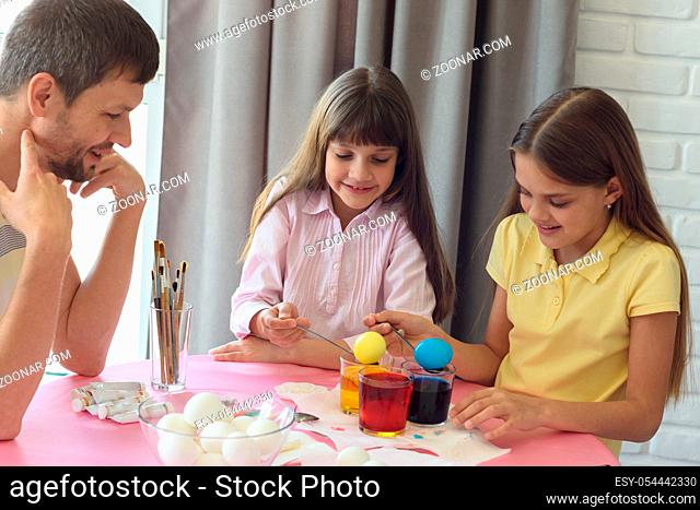 Children painted the first Easter eggs, dad watches them