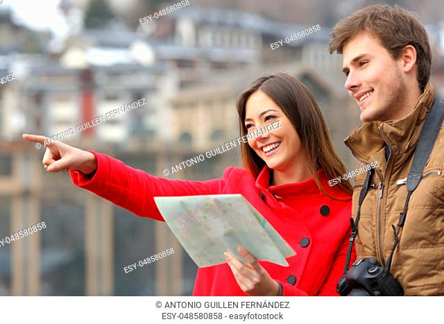 Happy couple of tourists holding a paper map and pointing away in the street of a town