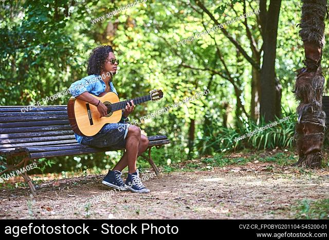 Musician playing guitar in a nice park