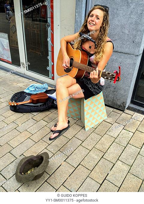 Tilburg, Netherlands. Young female musician playing the guitar and a harmonica, while singing songs in the streets