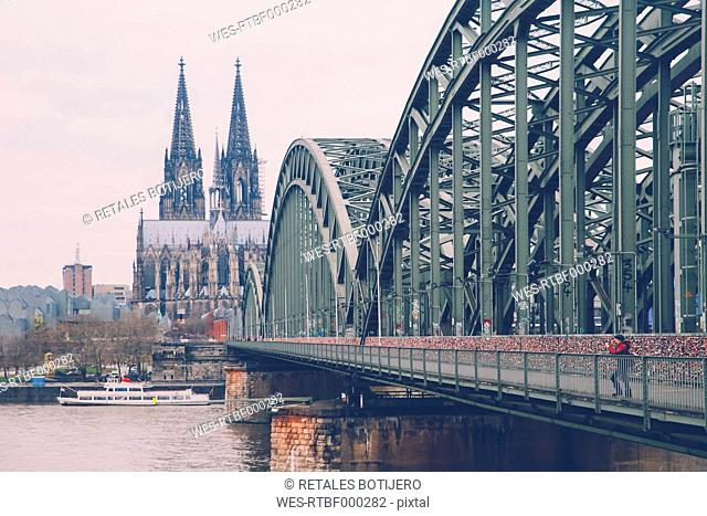 Germany, Cologne, woman taking picture at Hohenzollern Bridge