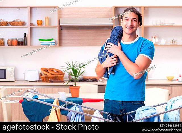 The young man husband doing clothing ironing at home