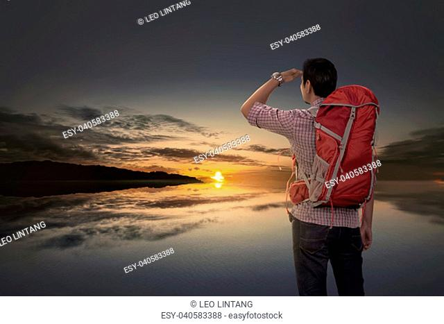 Rear view of asian tourist man with backpack looking at sunset view at lake
