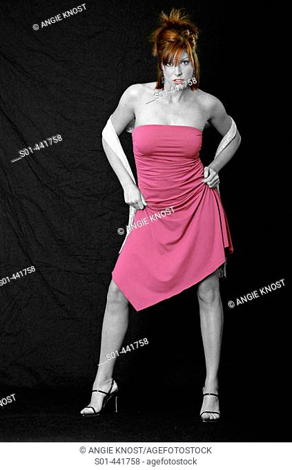 Selective color photo of woman with red hair in hot pink dress