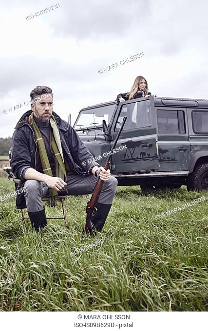 Man hunting, sitting in field with shot gun